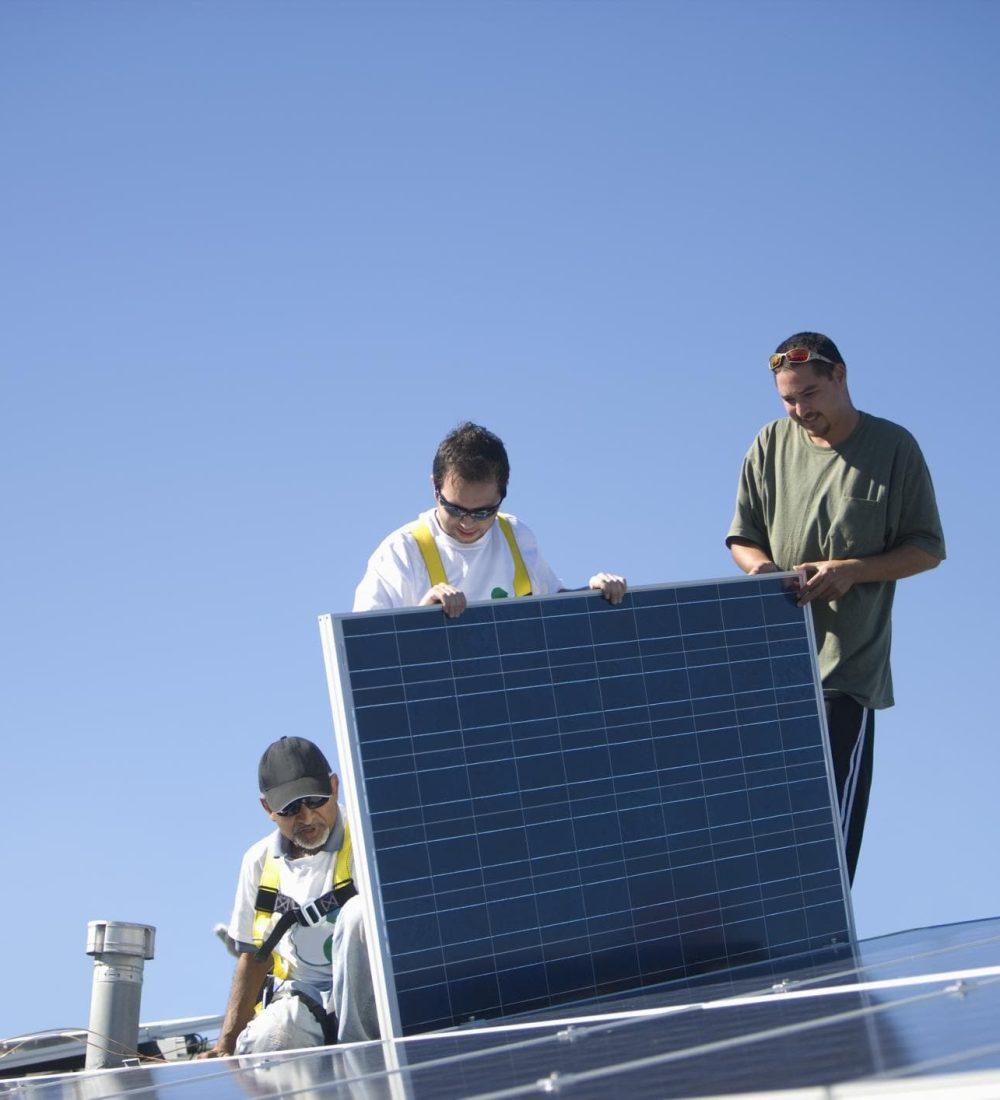 four men working on installing solar panels